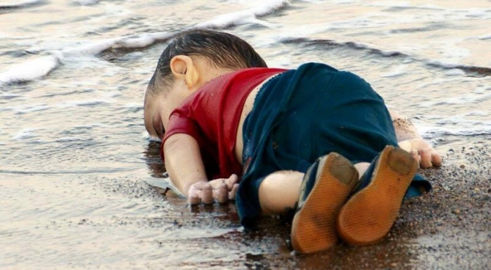 This photo is of Aylan Kurdi, a Syrian refugee child. His family attempted to cross from Bodrum, Turkey to Kos, Greece. He is one of 2,600 Syrian refugees who has died in their attempt to cross into Europe.